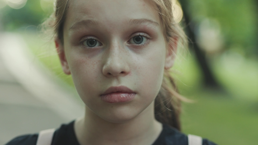 Close-up portrait of disappointed girl with deep green eyes looking attentively at camera. Serious female teenager. Outdoors. Summertime. Green background. | Shutterstock HD Video #1032638270
