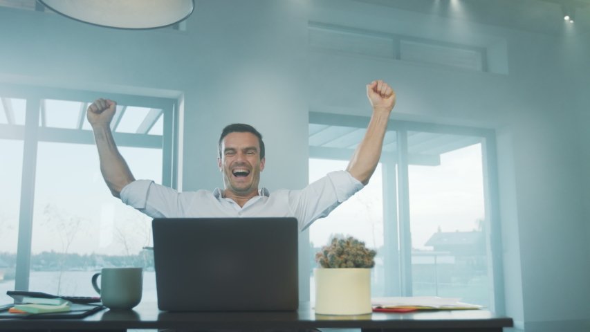 Happy business man reading good news on laptop computer at remote workplace. Freelance man enjoy succes in private house. Happy worker enjoy business victory at luxury house Royalty-Free Stock Footage #1032649505