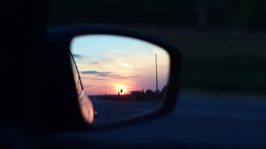 Car rear view mirror close up. Car driving long the road at sunset. Sunset in mirror reflection. Travelling by car concept.