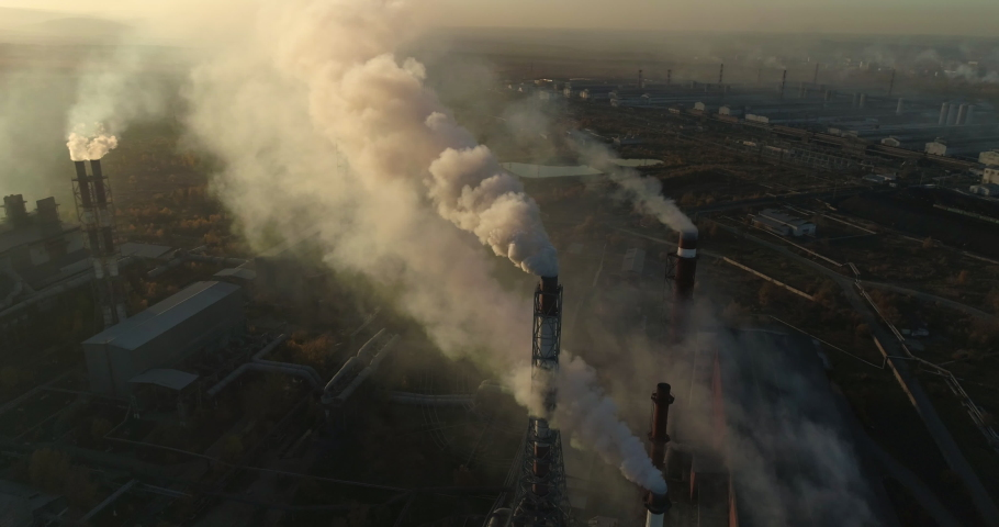 Aerial drone footage of steel factory pipes during sunset time. high above metallurgical plant and smoke cloud is coming from chimney. Aerial 4K