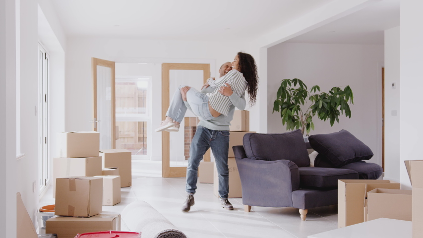 Man Carrying Woman Over Threshold Of New Home On Moving Day #1032653798