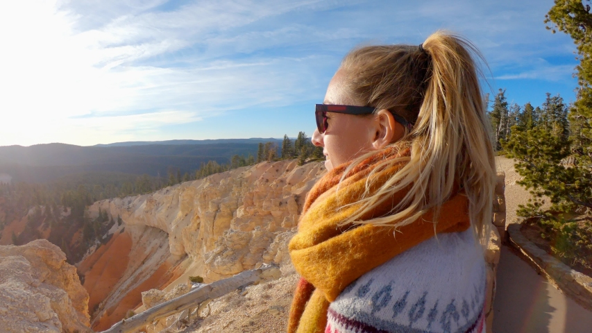 Young woman travels Bryce Canyon national park in Utah, United States, people travel explore nature. Girl hiking in red rock formations   Shutterstock HD Video #1032654935