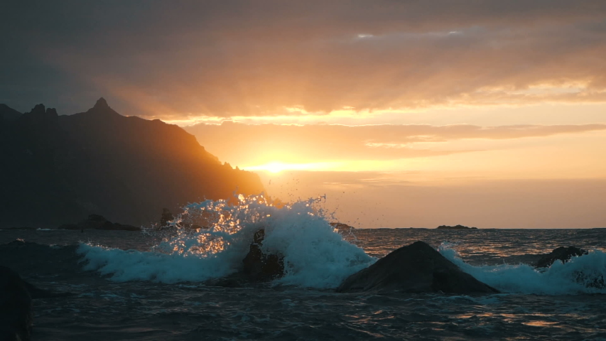 Waves rise in the air at beautiful sunset light at Benijo beach in Tenerife, Canary Islands. Big wave is crashing on rocks and spraying.