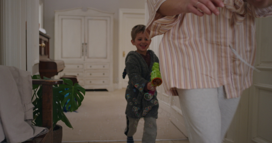 Cute little boy blowing bubbles chasing mother with toy gun running through house playing catch mom enjoying fun game with son enjoying weekend morning together 4k footage
