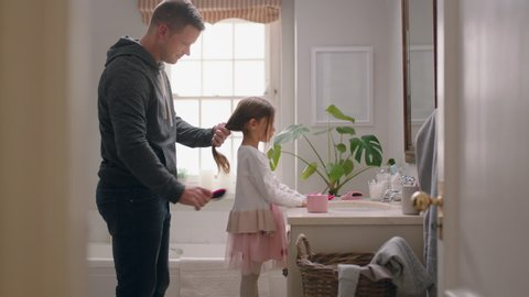 father brushing daughters hair in bathroom cute little girl getting ready in morning loving father enjoying parenthood caring for child