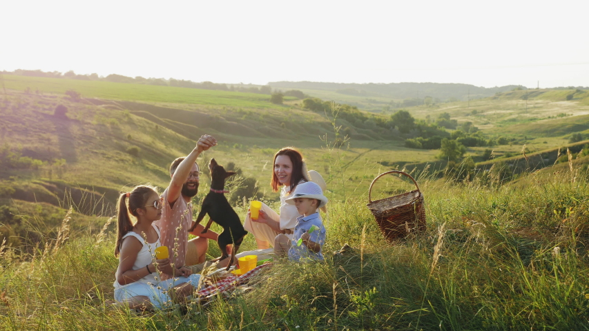 Family of four people on a picnic in the meadow at sunset. Family having fun, smiling, playing with their dog.