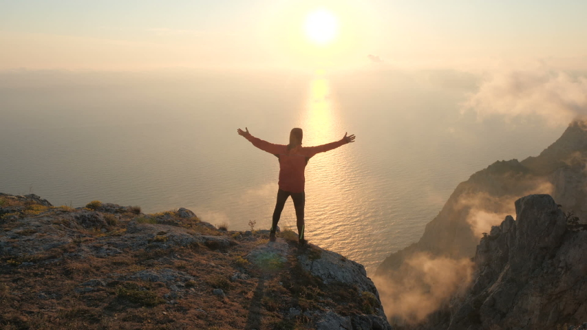 Silhuette of Young man arms outstretched observing beautiful dramatic colorful sunset above a sea from a high mountain in Crimea.   Shutterstock HD Video #1032681899