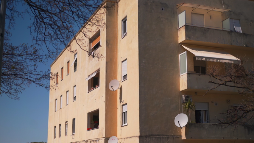 Boring, plain socialist architecture, apartment building with satellite TV antennas sticking out of the facade, soviet urban residential design and construction | Shutterstock HD Video #1032682040