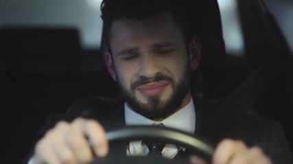 selective focus of upset bearded man crying while driving car