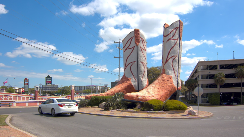 SAN ANTONIO, TX - 2019: World's Largest Cowboy Boots Public Art Attraction with Vehicles Driving by at North Star Mall on a Sunny Day in Texas
