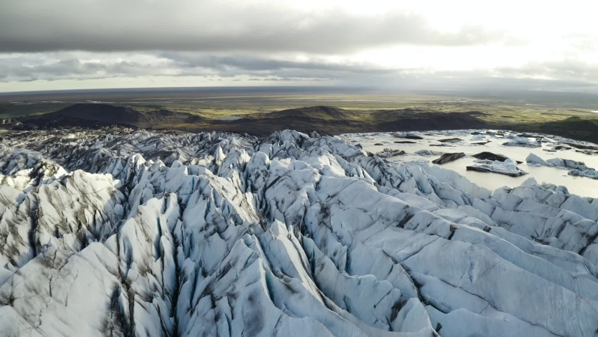 Aerial: Close up of Largest Glacier in Europe Vatnajokull Iceland Sunny day. Ridges with black ash. Melting ice. Concept of global warming
