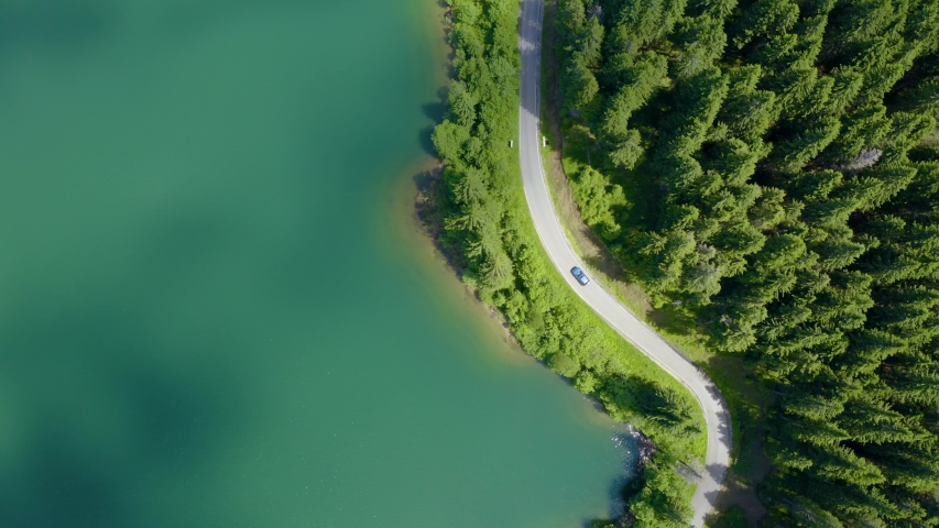 Aerial view of car driving through the forest and the lake on the side. Beautiful mountain road. Driving on the mountain road. Road trip. Mountain forest lake landscape Car driving through pine forest