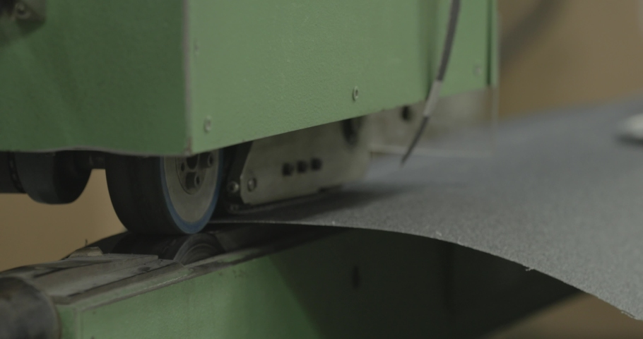 A large piece of sandpaper moves down an assembly line in a factory   Shutterstock HD Video #1032693116