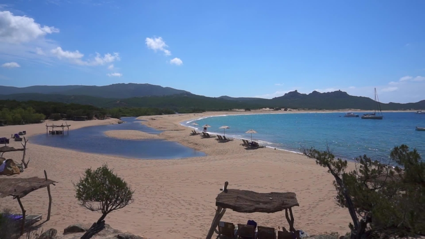 Corsica. Panorama of the sandy beach and blue sea on the island. Luxury beach. sun loungers. Sun protection. Moored sailing yachts at the coast. great place to stay
