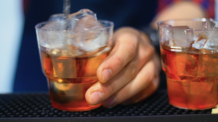 Professional barman mixing cocktail. Barman preparing cocktail at bar. Glass of brandy and ice cubes. Bartender stirring alcoholic drink with ice in glass. Human hand mixing whiskey with ice by spoon | Shutterstock HD Video #1032706088