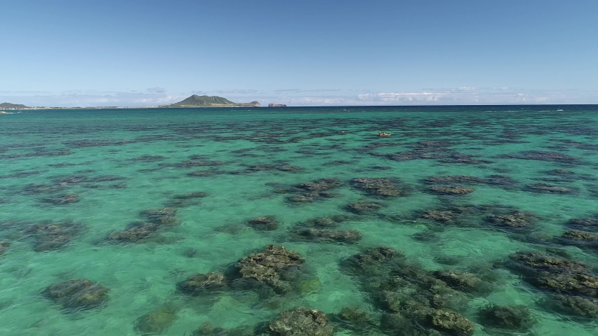 Aerial view of Lanikai beach, Honolulu, Hawaii, low angle view with drone cameraing forward, reef in clear green water with canoe | Shutterstock HD Video #1032719849