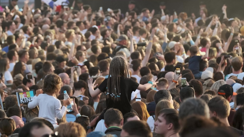Moscow - June 22, 2019: Crowd of fans cheering at open-air music festival, defocused #1032724523