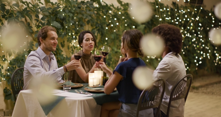 Four people, two couples happy talking and toasting with red wine during a romantic gourmet dinner or lunch. portrait medium shot.Friends italian trip in Umbria.4k slow motion
