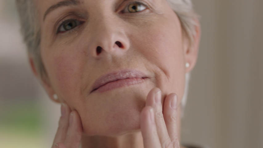 Portrait beautiful mature woman looking in mirror at perfect healthy skin touching face with hands enjoying smooth natural complexion with anti aging skincare getting ready at home beauty concept | Shutterstock HD Video #1032766835