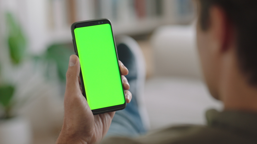 Young man using smartphone watching green screen enjoying entertainment on mobile phone chroma key display vertical orientation 4k footage