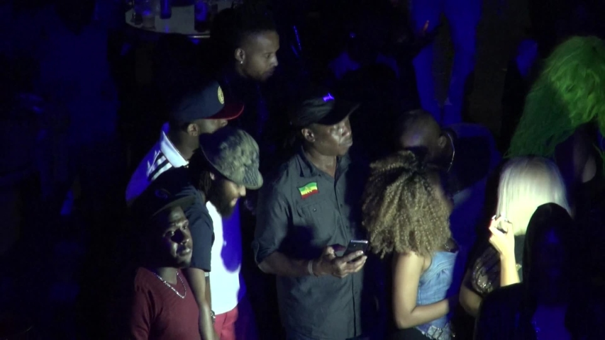 KINGSTON, JAMAICA - CIRCA JUNE 2017 : Scenery of outdoor street night club. Man and woman enjoying dance, popular night life for many Jamaican people. Reggae and hip hop music are played by DJ.   Shutterstock HD Video #1032767951