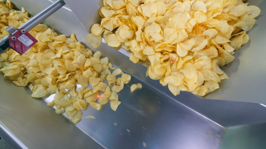 Two conveyors move potato chips at a food factory. | Shutterstock HD Video #1032769235