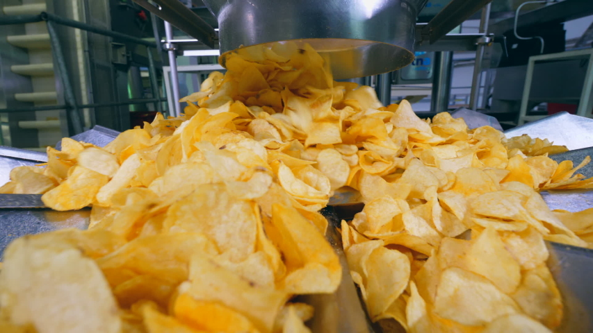 Yellow chips falling from a tube onto a plant conveyor. | Shutterstock HD Video #1032769244