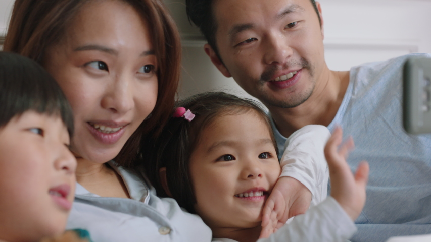 Happy asian family having video chat using smartphone in bed mother and father with children waving chatting to friends on mobile phone enjoying online communication 4k footage