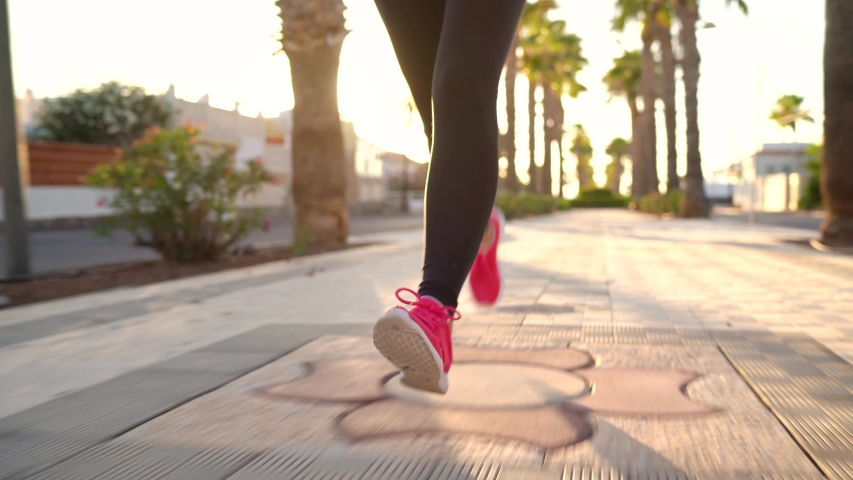 Close up of woman running along the palm avenue at sunset #1032774851