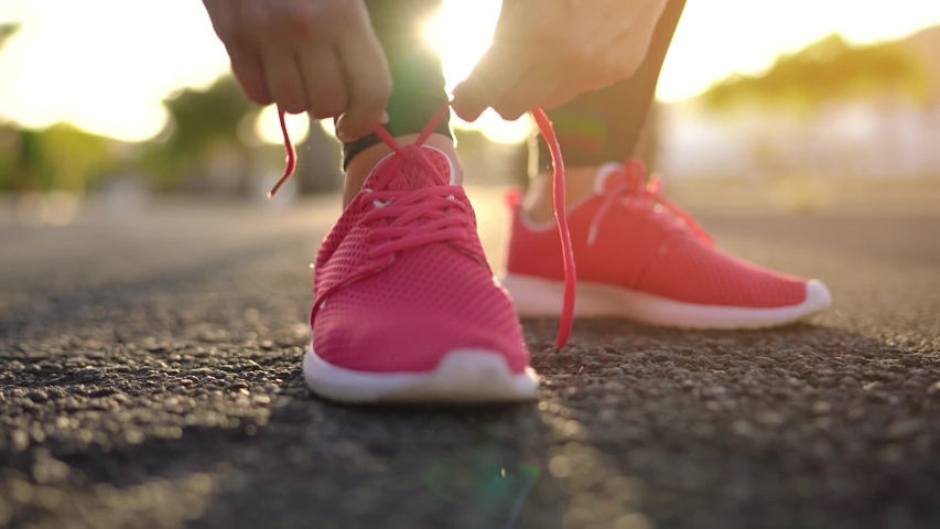 Close up of woman tying shoe laces and running along the palm avenue at sunset. Slow motion | Shutterstock HD Video #1032774866