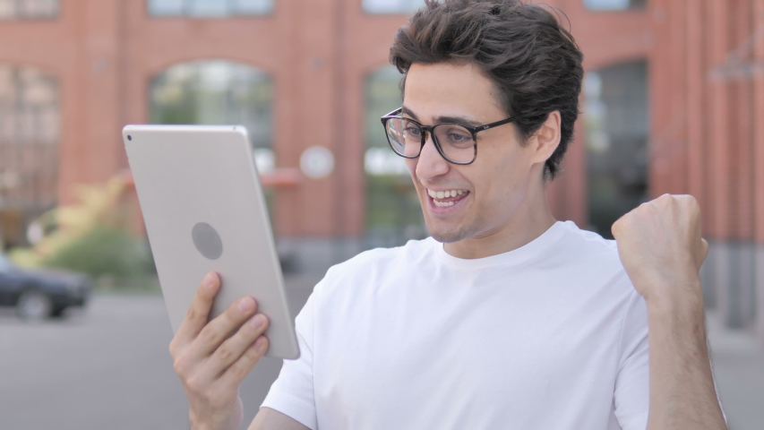 Outdoor Portrait of Young Man Celebrating Success on Tablet | Shutterstock HD Video #1032775871