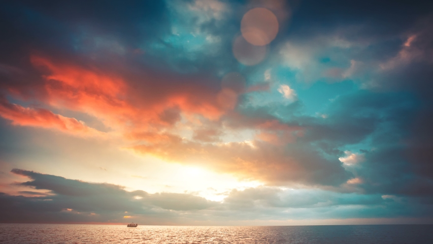 Romantic colorful sunset at the sea. Sun go down, blue and orange clouds flow in sky. Majestic summer landscape. Exploring beauty world, travel, holidays, recreation. Slow motion timelaps 4K footage | Shutterstock HD Video #1032785225