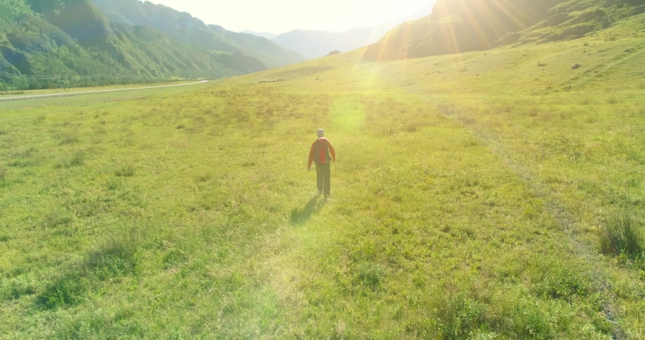 Aerial 4K UHD view. Low altitude flight over young man tourist walking across green mountain field. Huge rural valley and sunny meadow at summer day. Backpack hiking guy.   Shutterstock HD Video #1032787136