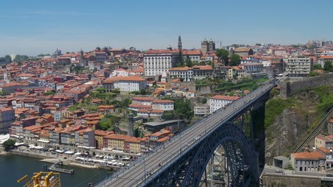 Aerial footage of douro riverside panning and rotating over The Dom Luís I Bridge in Porto city, Portugal