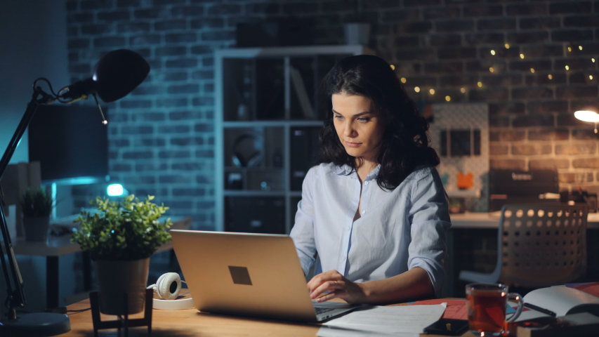 Businesswoman attractive young girl is leaving workplace late at night turning off light and laptop and going away from dark empty room. People and business concept. Royalty-Free Stock Footage #1032818378