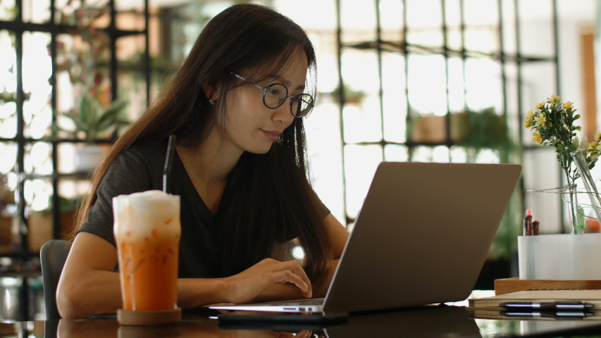 Asian Woman Works on a Laptop while Sitting in Cafe. | Shutterstock HD Video #1032818636