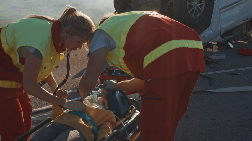 On the Car Crash Traffic Accident Scene: Paramedics Saving Life of a Little Girl Lying on Stretchers, She's given Best First Aid Help. Professional Medics Doing their Job Best | Shutterstock HD Video #1032835988