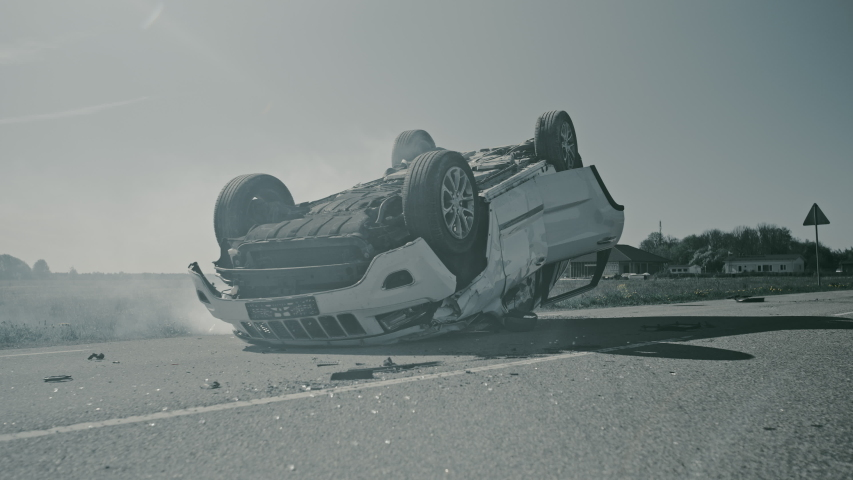 Horrific Traffic Accident Rollover Smoking and Burning Vehicle Lying on its Roof in the Middle of the Road after Collision. Daytime Crash Scene with Damaged Car. Shot In Black and White | Shutterstock HD Video #1032836069