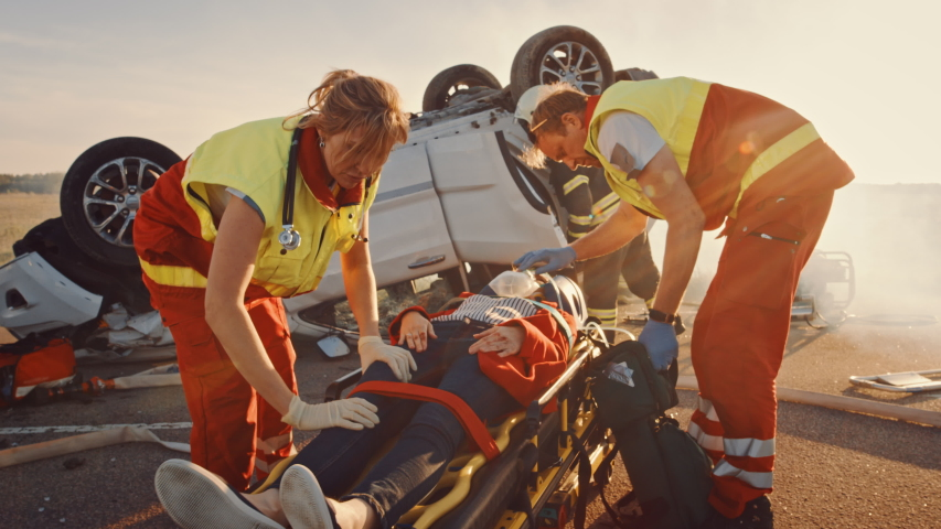 On the Car Crash Traffic Accident Scene: Paramedics Save Life of a Female Victim Lying on Stretchers. They Listen To a Heartbeat, Apply Oxygen Mask and Give First Aid. Firefighters Extinguish Fire