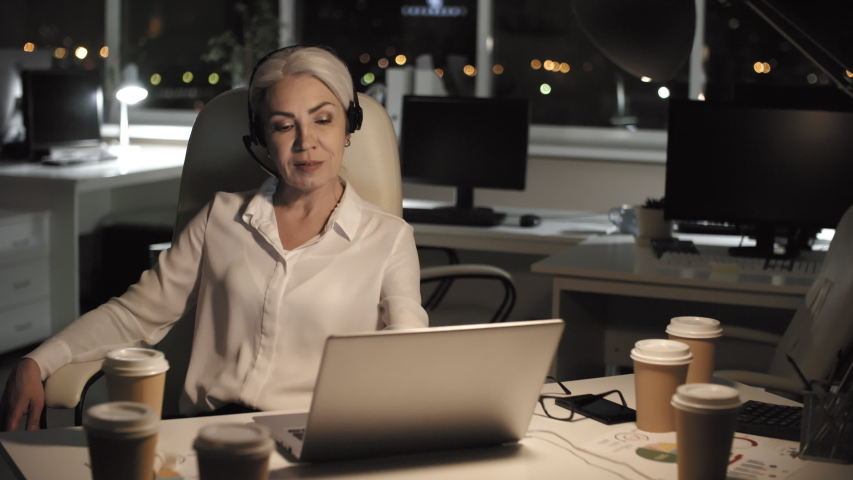 Waist-up shot of smiling grey-haired Caucasian businesswoman, dressed in white blouse and wearing headset, sitting alone late at night in dark office with coffee and participating in conference call | Shutterstock HD Video #1032843470