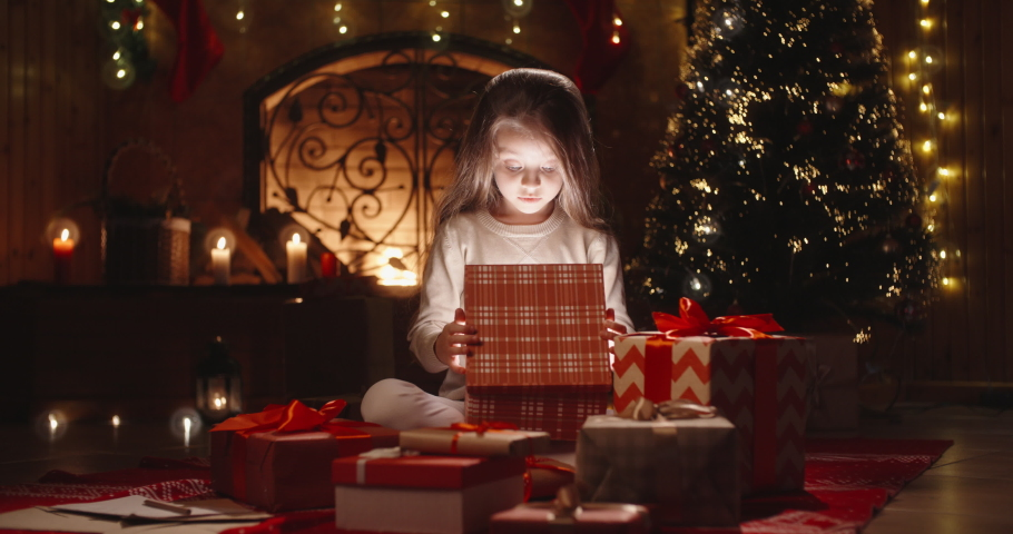 Little caucasian girl sitting near christmas tree in decorated room and opening her gift with something special - holidays and celebrations, christmas spirit concept close up 4k footage