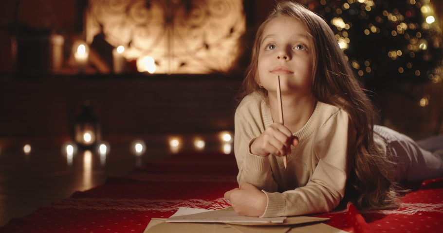 Sweet caucasian child is writing a letter to santa claus in room, decorated for christmas, preparing for holiday -christmas spirit, holidays and celebrations concept close up 4k footage