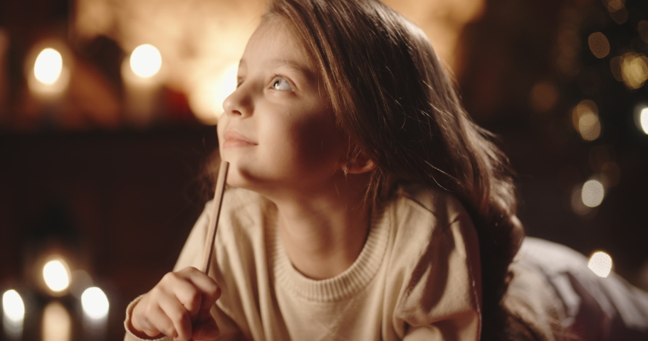 Cute little girl is lying on carpet in room decorated for christmas, writing a letter for santa, preparing for holiday - christmas spirit concept close up 4k footage