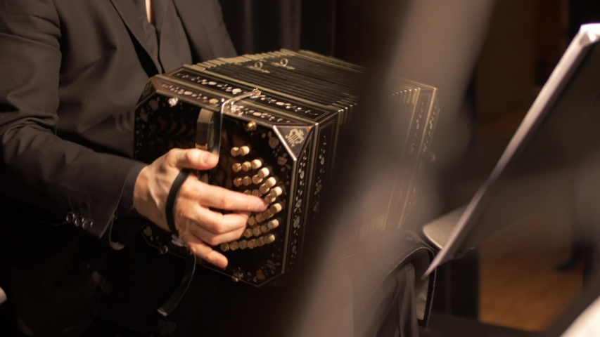 A Bandoneon accordion player is practicing for a tango music show, while a music stand is blurred in the foreground.
