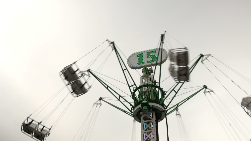 Rotating tall-high carousel with flying people on sky background. Royalty-Free Stock Footage #1032861266