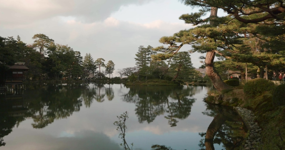 Beautiful mirror like lake with trees glowing golden with the setting sun in a traditional Japanese garden | Shutterstock HD Video #1032872144