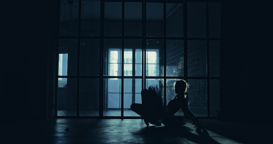 Dancer warms up the muscles of the legs, the silhouette of the figure. Dark hall. | Shutterstock HD Video #1032886433