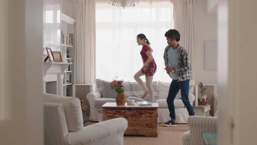 Happy father and daughter dancing at home teenage girl having fun dance with dad celebrating weekend together 4k footage