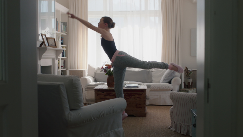 beautiful teenage girl dancing at home practicing ballet dance moves having fun rehearsing in living room #1032902924