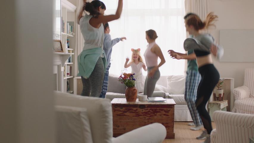 happy multiracial family dancing at home having fun enjoying dance celebrating exciting weekend together wearing pajamas #1032902936